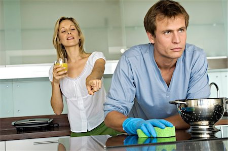 dominant woman - Smiling woman pointing at angry man holding sponge Stock Photo - Premium Royalty-Free, Code: 6108-05858959