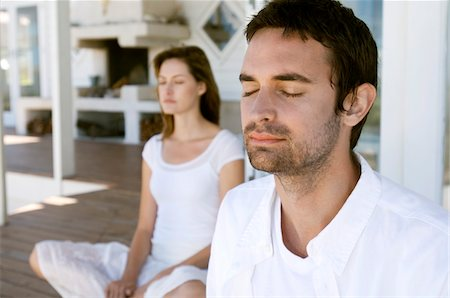 Couple sitting cross-legged on wooden terrace, eyes closed Stock Photo - Premium Royalty-Free, Code: 6108-05858971