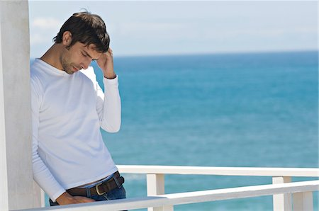 Young thinking man leaning against wall on a terrace, sea in background Stock Photo - Premium Royalty-Free, Code: 6108-05859068