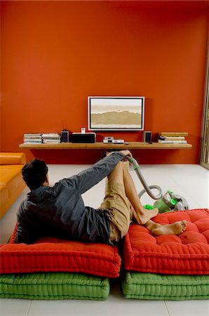 plasma - Man watching TV lying on cushions, vacuum cleaner in front of him Stock Photo - Premium Royalty-Free, Code: 6108-05859023