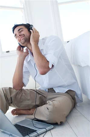 Young man listening to music with laptop Stock Photo - Premium Royalty-Free, Code: 6108-05859024