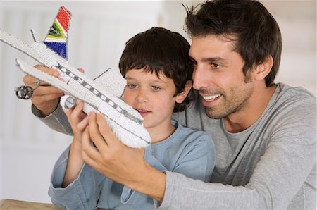 Father and son playing with model aeroplane Stock Photo - Premium Royalty-Free, Code: 6108-05859163