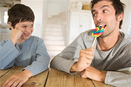 Father eating lollipop with his son Stock Photo - Premium Royalty-Free, Code: 6108-05859166