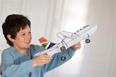 Little boy playing with model aeroplane Stock Photo - Premium Royalty-Free, Code: 6108-05859171