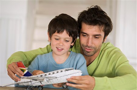 Father and son playing with model aeroplane Stock Photo - Premium Royalty-Free, Code: 6108-05859199