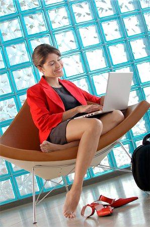 Businesswoman using laptop, smiling Stock Photo - Premium Royalty-Free, Code: 6108-05859286
