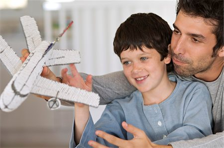 Father and son playing with model aeroplane Stock Photo - Premium Royalty-Free, Code: 6108-05859204