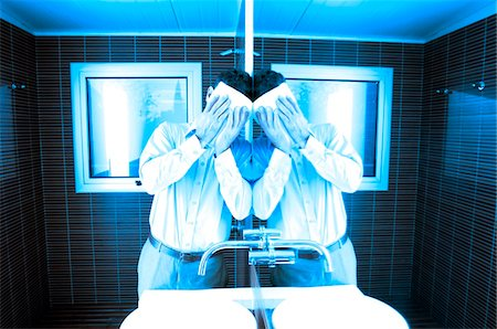 Man covering face while leaning by mirror in washroom Stock Photo - Premium Royalty-Free, Code: 6108-05859394