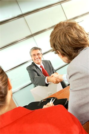 Two businessmen shaking hands in office Stock Photo - Premium Royalty-Free, Code: 6108-05859468