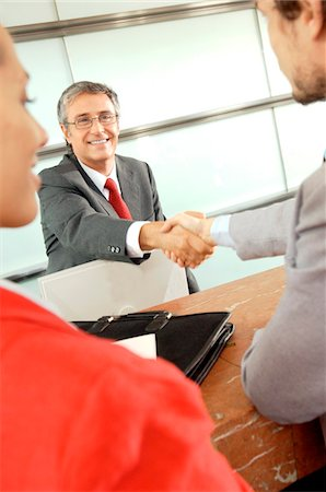 Business people shaking hands in office, smiling Stock Photo - Premium Royalty-Free, Code: 6108-05859415