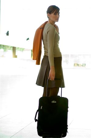 Businesswoman standing with her luggage at an airport Stock Photo - Premium Royalty-Free, Code: 6108-05859669