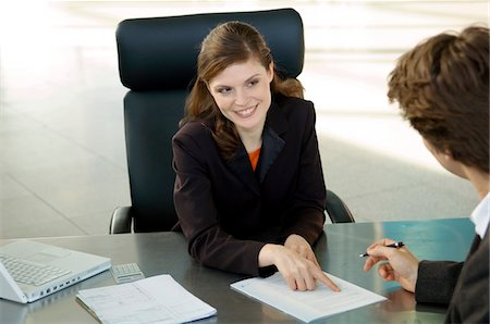 Businesswoman pointing at a contract and businessman sitting in front of her Stock Photo - Premium Royalty-Free, Code: 6108-05859687