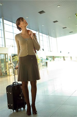 Businesswoman standing with her luggage at an airport lounge Stock Photo - Premium Royalty-Free, Code: 6108-05859698