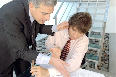 pulling - Businessman holding ear of employee in office Stock Photo - Premium Royalty-Free, Code: 6108-05859631