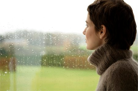 Mid adult woman looking out through a window Stock Photo - Premium Royalty-Free, Code: 6108-05859776