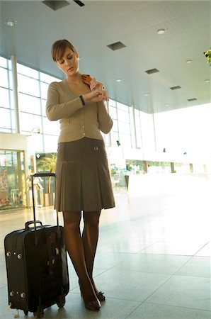 Low angle view of a businesswoman checking the time at an airport Stock Photo - Premium Royalty-Free, Code: 6108-05859713