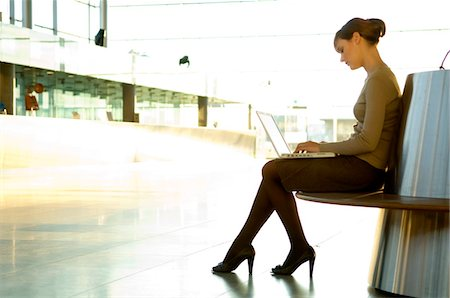 Side profile of a businesswoman using a laptop at an airport lounge Stock Photo - Premium Royalty-Free, Code: 6108-05859712