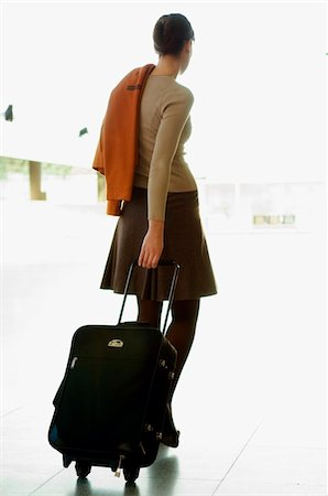 Rear view of a businesswoman pulling her luggage at an airport Stock Photo - Premium Royalty-Free, Code: 6108-05859721