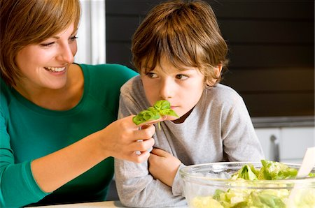 smelly - Close-up of a young woman feeding basil to her son Stock Photo - Premium Royalty-Free, Code: 6108-05859898