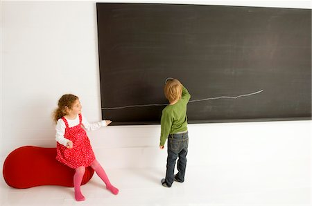 pantyhose kid - Rear view of a boy drawing on a blackboard with his sister sitting beside him Stock Photo - Premium Royalty-Free, Code: 6108-05860242