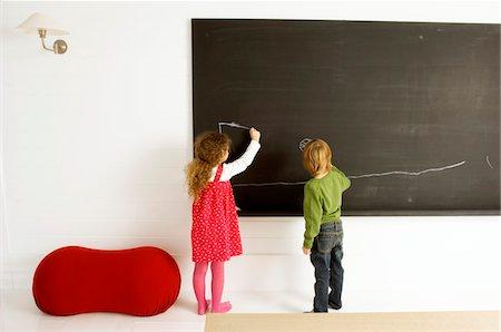 pantyhose kid - Two children drawing on a blackboard Stock Photo - Premium Royalty-Free, Code: 6108-05860263