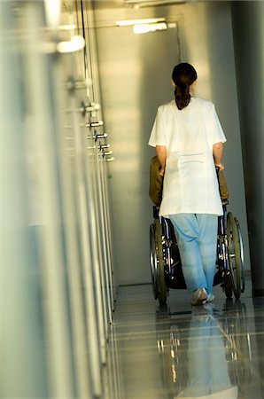 patient walking hospital halls - Rear view of a female doctor pushing a patient sitting in a wheelchair Stock Photo - Premium Royalty-Free, Code: 6108-05860329