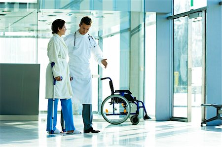 patient walking hospital halls - Male doctor assisting a female patient in walking on crutches Stock Photo - Premium Royalty-Free, Code: 6108-05860443