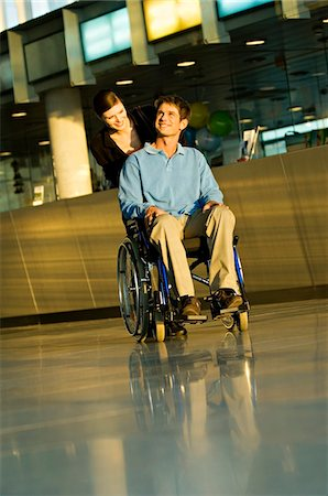patient walking hospital halls - Young woman pushing a male patient sitting in a wheelchair Stock Photo - Premium Royalty-Free, Code: 6108-05860440