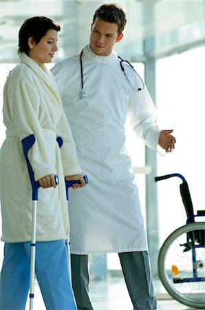 patient walking hospital halls - Male doctor assisting a female patient in walking on crutches Stock Photo - Premium Royalty-Free, Code: 6108-05860441