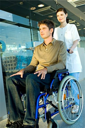patient walking hospital halls - Female doctor pushing a male patient sitting in a wheelchair Stock Photo - Premium Royalty-Free, Code: 6108-05860442