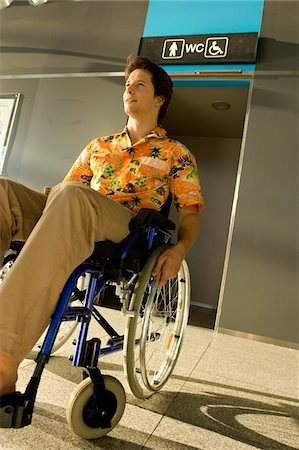 Mid adult man sitting in a wheelchair in front of a restroom entrance Stock Photo - Premium Royalty-Free, Code: 6108-05860446
