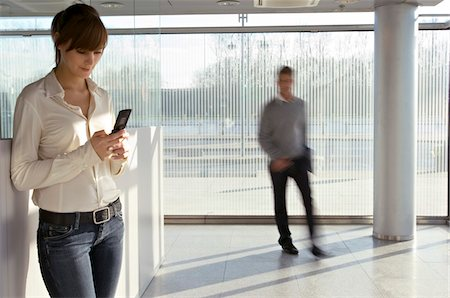 Businesswoman using a mobile phone with a businessman walking in the background Stock Photo - Premium Royalty-Free, Code: 6108-05860458