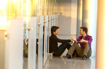 Two businessmen sitting in a corridor and talking with each other Stock Photo - Premium Royalty-Free, Code: 6108-05860497