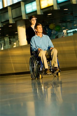 patient walking hospital halls - Young woman pushing a male patient sitting in a wheelchair Stock Photo - Premium Royalty-Free, Code: 6108-05860412