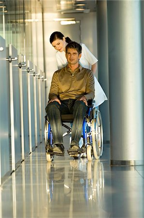 patient walking hospital halls - Female doctor pushing a male patient sitting in a wheelchair Stock Photo - Premium Royalty-Free, Code: 6108-05860433