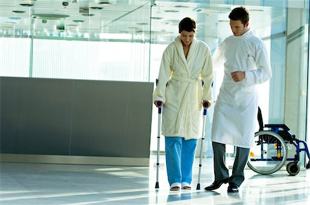 patient walking hospital halls - Male doctor assisting a female patient in walking on crutches Stock Photo - Premium Royalty-Free, Code: 6108-05860430