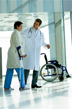 patient walking hospital halls - Male doctor assisting a female patient in walking on crutches Stock Photo - Premium Royalty-Free, Code: 6108-05860439