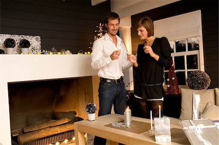 Mid adult man and a young woman lighting a candle with a cigarette lighter Stock Photo - Premium Royalty-Free, Code: 6108-05860662