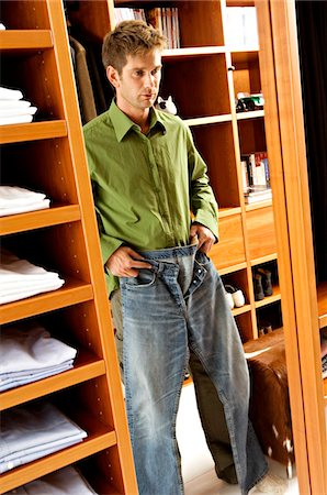 Reflection of a mid adult man getting dressed Stock Photo - Premium Royalty-Free, Code: 6108-05860768