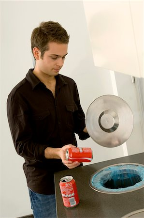 Young man putting a drink can in a garbage bin Stock Photo - Premium Royalty-Free, Code: 6108-05860772