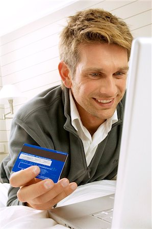 ebusiness - Mid adult man working on a laptop and holding a credit card Stock Photo - Premium Royalty-Free, Code: 6108-05860791