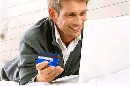 ebusiness - Mid adult man working on a laptop and holding a credit card Stock Photo - Premium Royalty-Free, Code: 6108-05860801