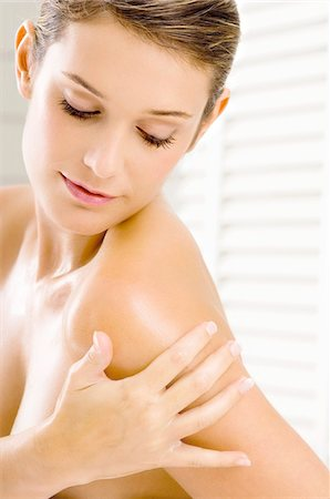 Close-up of a young woman applying moisturizer on her shoulder Stock Photo - Premium Royalty-Free, Code: 6108-05860961