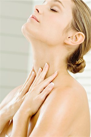 Close-up of a young woman applying moisturizer on her neck Stock Photo - Premium Royalty-Free, Code: 6108-05860910