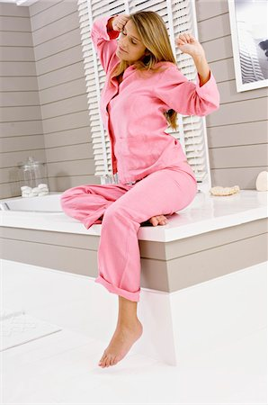 Young woman sitting on a bathtub and stretching Stock Photo - Premium Royalty-Free, Code: 6108-05860919