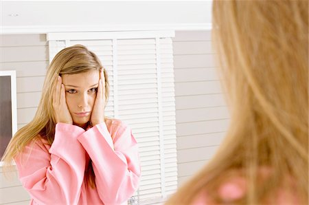 Reflection of a young woman in a mirror looking sad Stock Photo - Premium Royalty-Free, Code: 6108-05860925