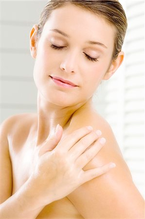 Close-up of a young woman applying moisturizer on her shoulder Stock Photo - Premium Royalty-Free, Code: 6108-05860932