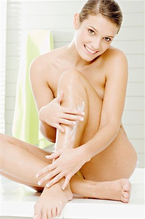Portrait of a young woman applying moisturizer on her leg Stock Photo - Premium Royalty-Free, Code: 6108-05860938