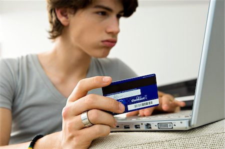 ebusiness - Close-up of a teenage boy using a laptop and holding a credit card Stock Photo - Premium Royalty-Free, Code: 6108-05861037