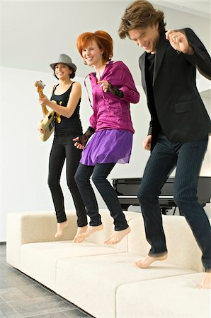 Two young women and a teenage boy dancing on a couch Stock Photo - Premium Royalty-Free, Code: 6108-05861159